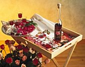 Bouquet of roses, bottle &  glasses of rose liqueur on tray