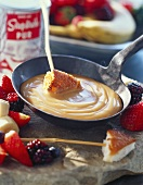 Sweet fondue with custard, cake and fruit
