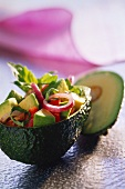 Avocado and tomato salad served in a hollowed-out avocado