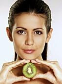 Woman holding half a kiwi fruit