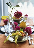 Table laid in autumnal style with pumpkins and dahlias