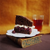 A piece of chocolate cherry cake standing on a book