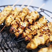 Barbecued chicken kebabs on a grill rack