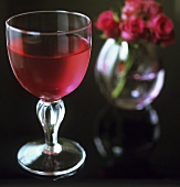 A glass of rosé wine and roses