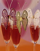 Three glasses of Kir Royal decorated with butterflies