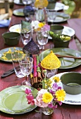 A table laid with green tableware in open air