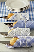 Four sets of cutlery and bread rolls tied in napkins