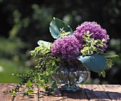 Two Allium flowers, hosta leaves and ivy in a glass vase