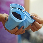 Hands holding three plastic pots with compost and seeds