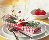 Napkin decorated for Christmas with star and sprig of fir