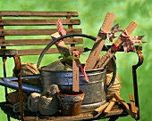 Old garden chair with watering can, wooden rulers, yardstick