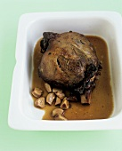 Leg of lamb in a roasting dish with garlic and sherry sauce