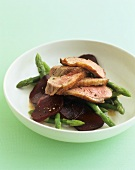 Duck in orange sauce on green asparagus and beetroot