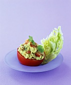 A tomato stuffed with avocado and salad