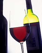 A glass of red wine with a bottle in the background
