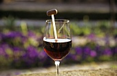 A glass of red wine with wine thermometer