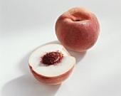 Peach (Prunus persica), variety 'Snow King', whole and halved