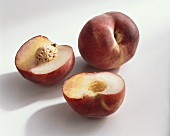 Peach, variety 'September Sun', whole and halved