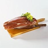 Raw Schinkenspeck ham on a wooden board