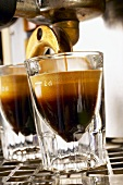 Espresso running into two espresso glasses