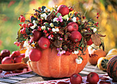Hollowed-out pumpkin with apples, snowberries & spindle berries