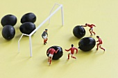 Miniature footballers attacking the goal with olives