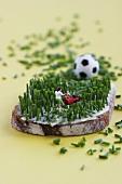 Miniaturfussballer mäht ein Schnittlauch-Butter-Brot