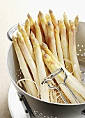 White asparagus spears with asparagus peeler in colander