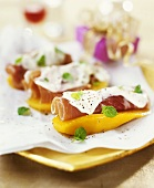 Ham rolls with sour cream on mango slices