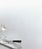 Silver cutlery on napkin and white wine glass