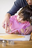 Mother and daughter cutting out biscuits