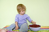 Small boy eating redcurrants out of a bowl