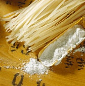 Rice flour on wooden scoop and rice noodles