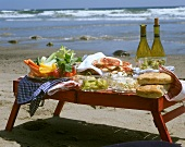 Picnic table on beach with pizza, vegetable snacks & wine