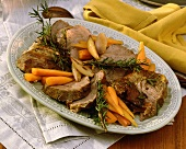 Pieces of roast veal with rosemary, carrots, garlic on plate