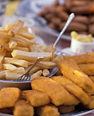 Plate of chips, several fish fingers beside it