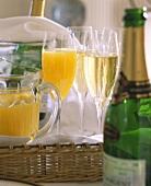 Glasses & bottles of champagne, glass & jug of orange juice