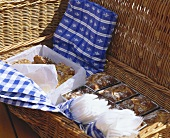 Picnic basket with various breads, cakes & plastic cutlery