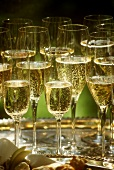Lots of half-full glasses of champagne on silver tray