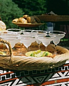 Several glasses of Margarita cocktails on wicker tray