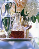 Sherry in glass & crystal carafe; silver jug; flowers