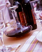 Red wine bottles, carafe and glasses on laid table