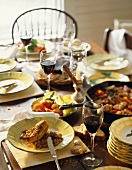 Rustic table laid with Mediterranean dishes & red wine
