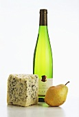 A piece of blue cheese, a pear and bottle of Gewürztraminer
