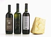 Piece of Parmesan and suitable red and white wine in bottles