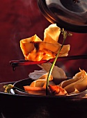 Filled wonton on chopsticks with soy sauce