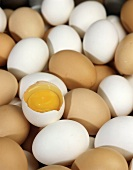 Many brown and white eggs, one broken open