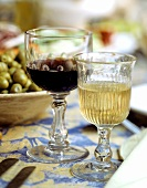 Two rustic glasses with red and white wine