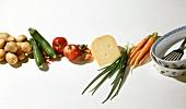 Verschiedene Gemüsesorten, rote Äpfel, Käse, Auflaufformen
