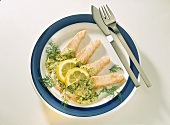Strips of salmon with dill & ginger sauce and lemon slices